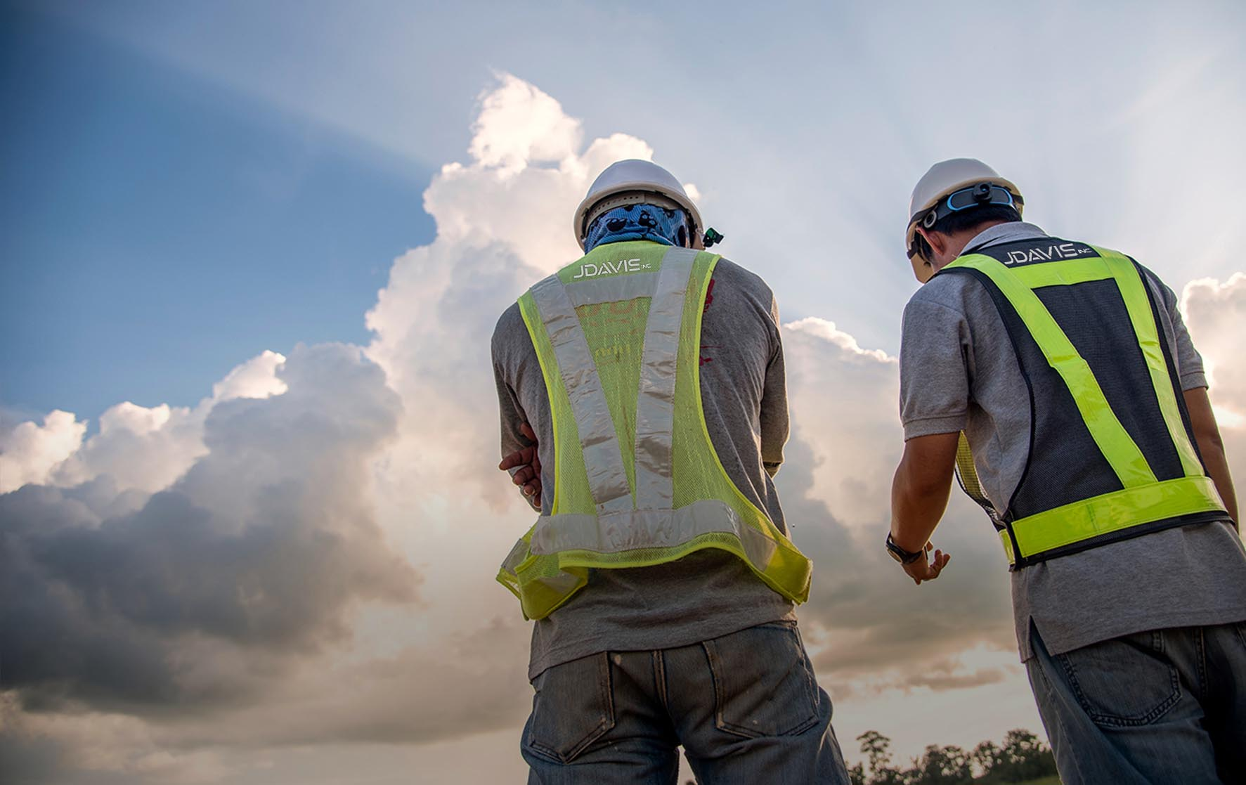 heroic angle photo of two construction workers with dramatic sky