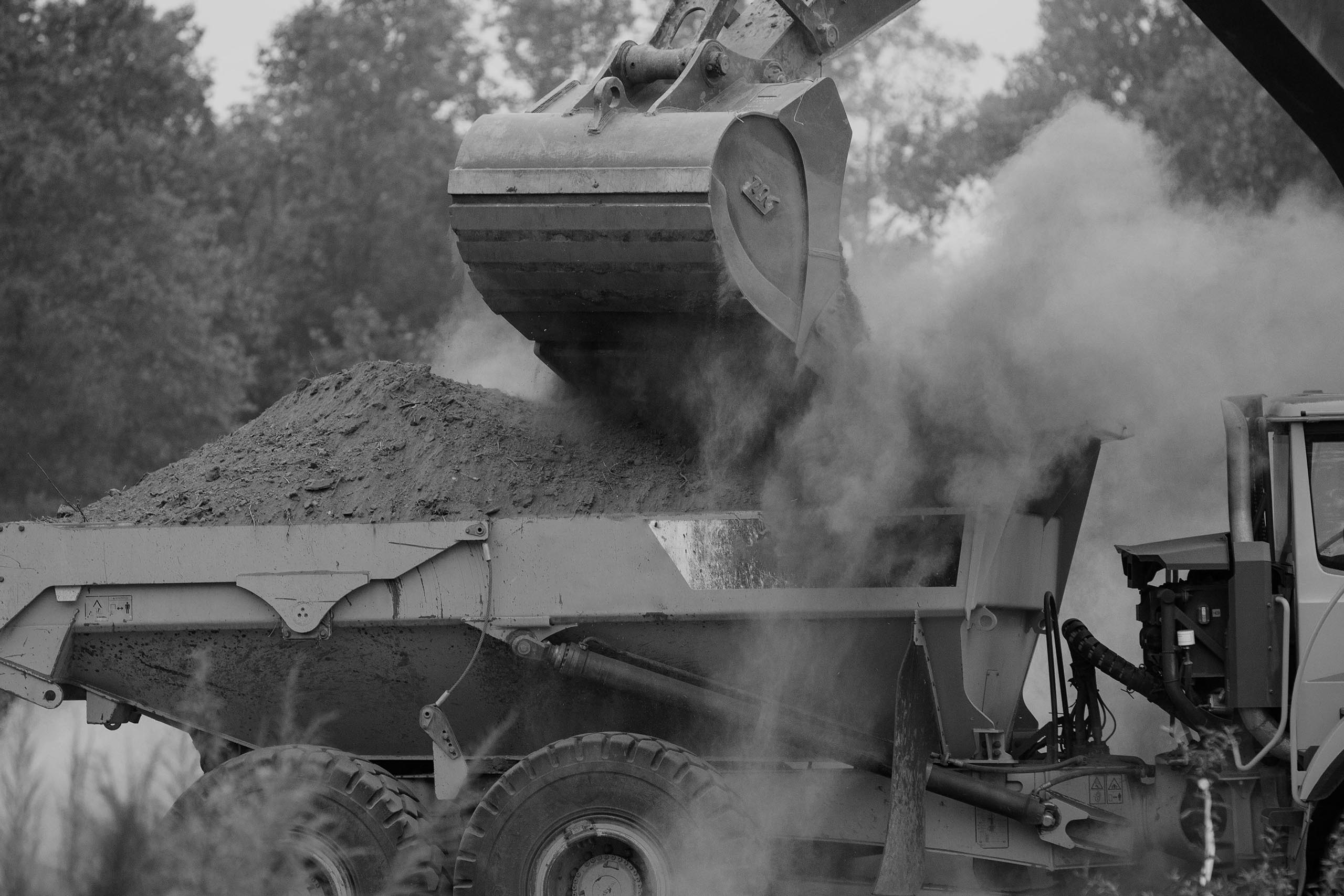 black and white image of excavator bucket dumping dirt in truck
