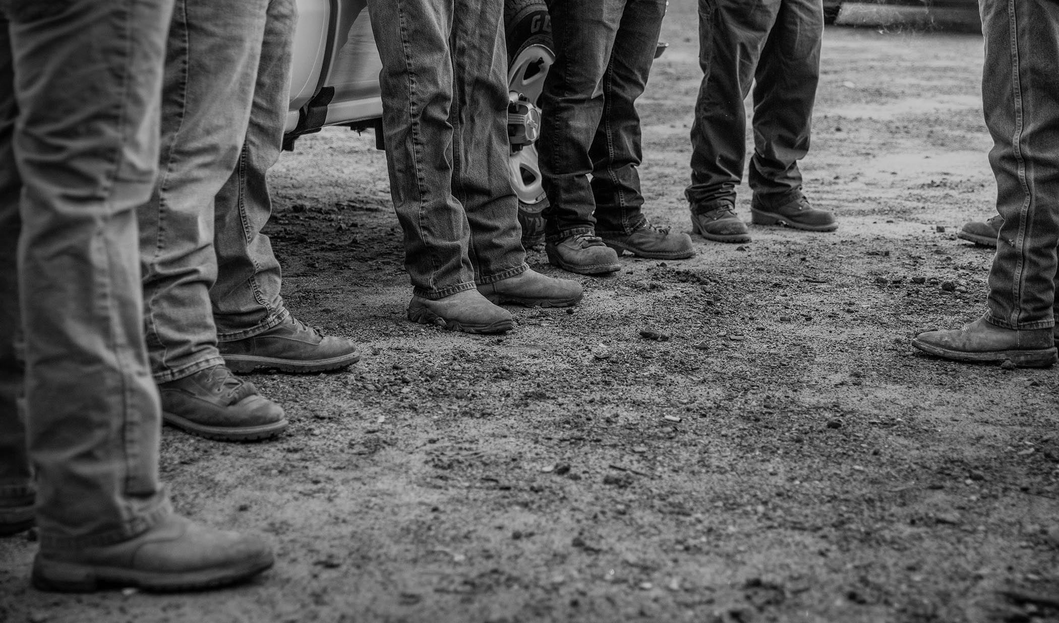 bw closeup of a group of construction workers focused on their boots