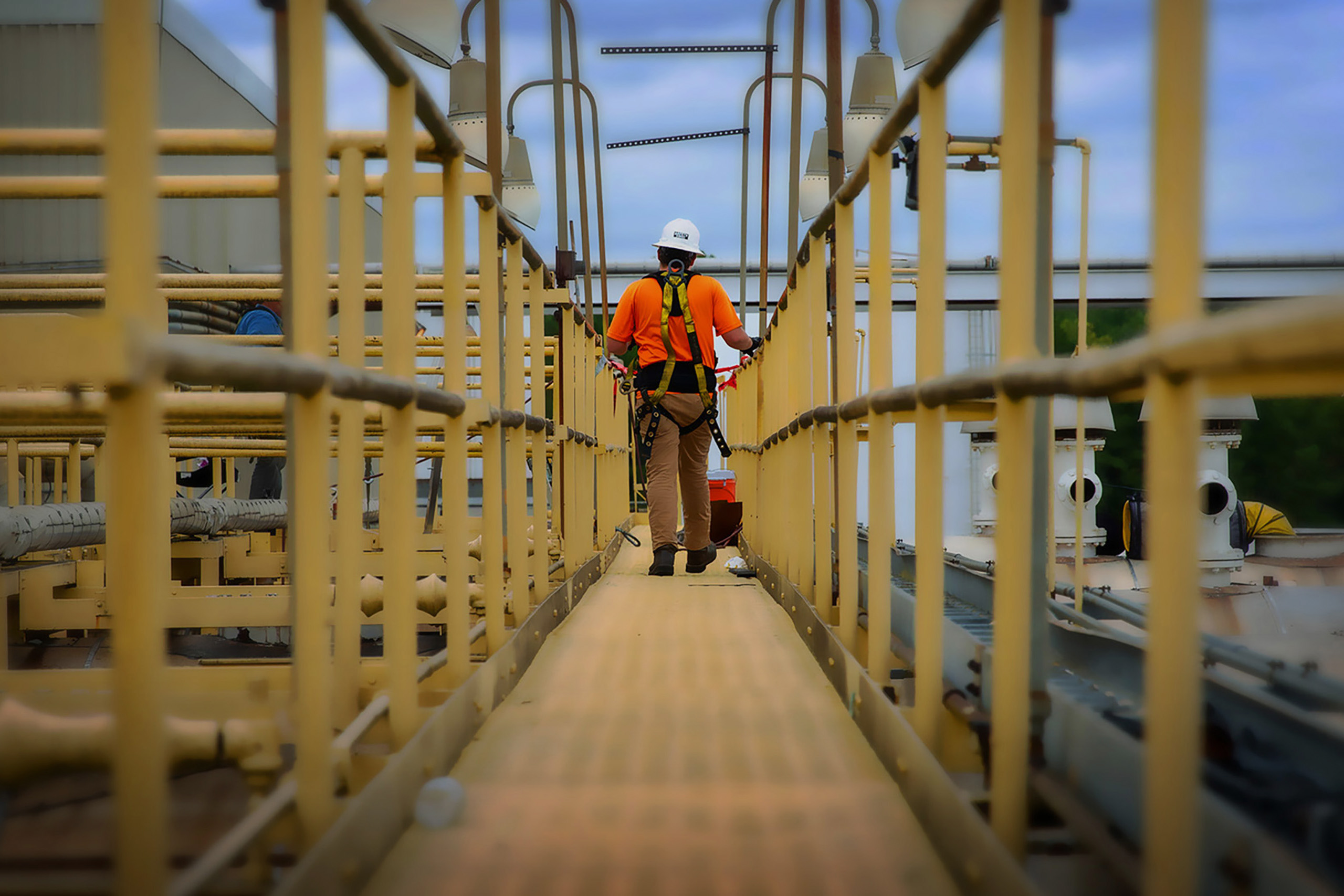 industrial worker walking away down a long metal walkway