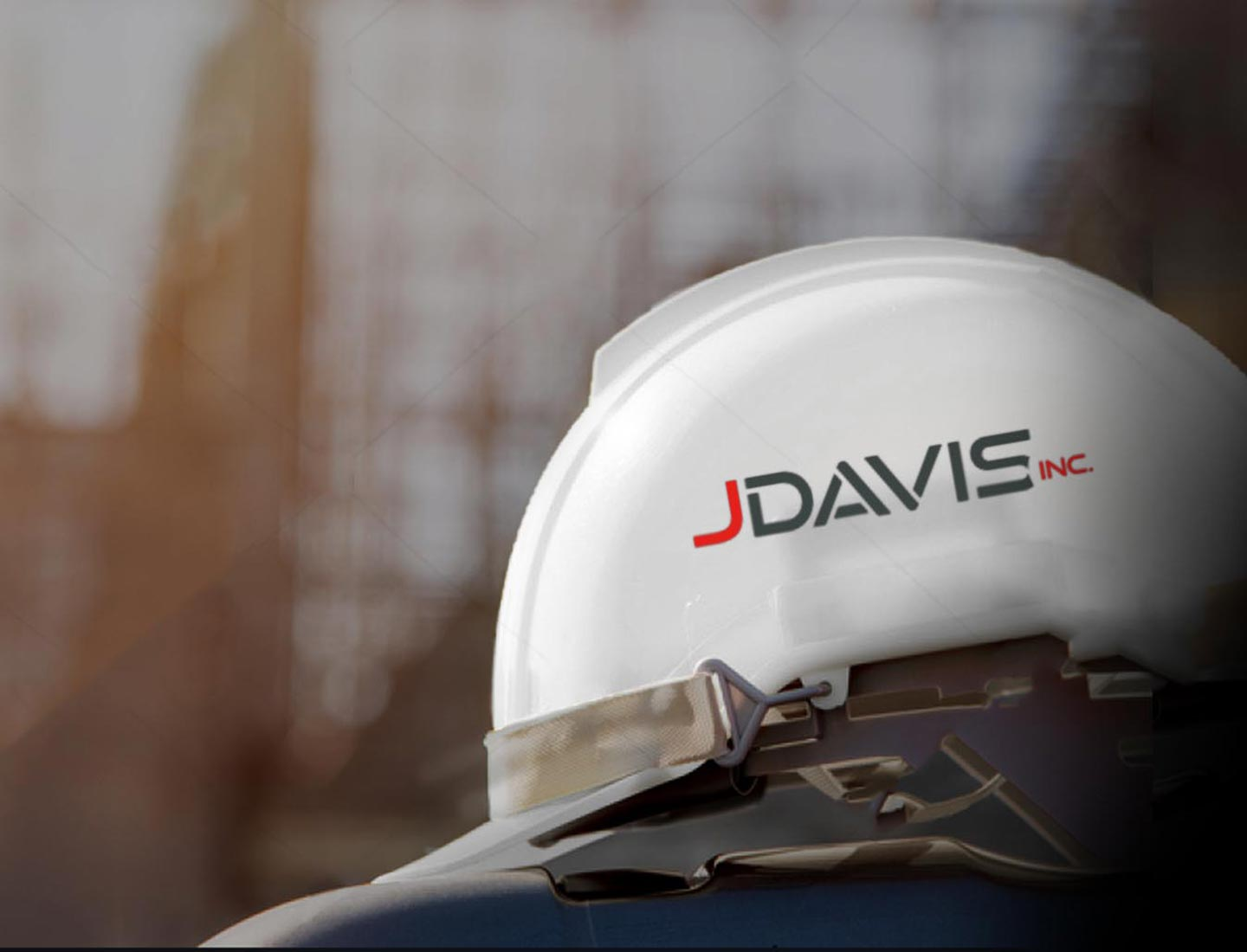 jdavis inc logo on white hardhat with a blurry construction site background